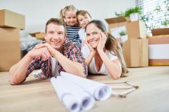 Glückliche Familie und Kinder nach dem Umzug in neuer Wohnung oder Eigenheim
